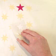 1. Selbstklebende Schablone von der Folie ablösen und auf dem Stoff andrücken.