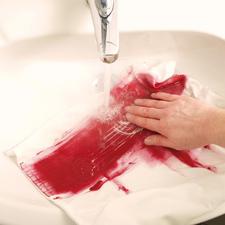 4. Anschließend den Stoff mit reichlich klarem Wasser per Hand ausspülen, sodass die überschüssige Farbe ausgewaschen wird.  Jetzt wird auch der Blockiereffekt sichtbar. Die Textilfarbe haftet nur dort auf dem Stoff, wo er nicht mit der Farbblockierer behandelt wurde.