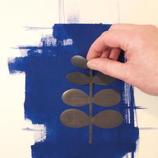 2. Jetzt ziehen Sie einfach die Folie von einer der mitgelieferten Schablonen. Die Schablone nun auf die nasse Farbe legen.